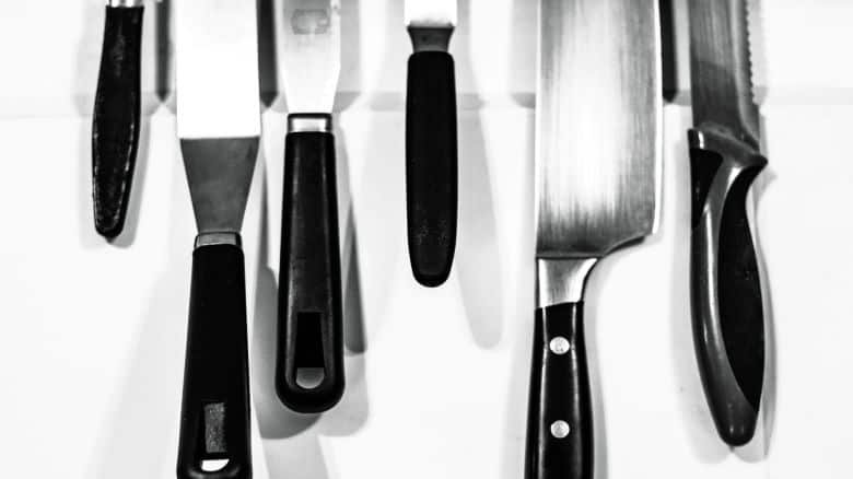 Kitchen knives hanging from a magnetic knife holder