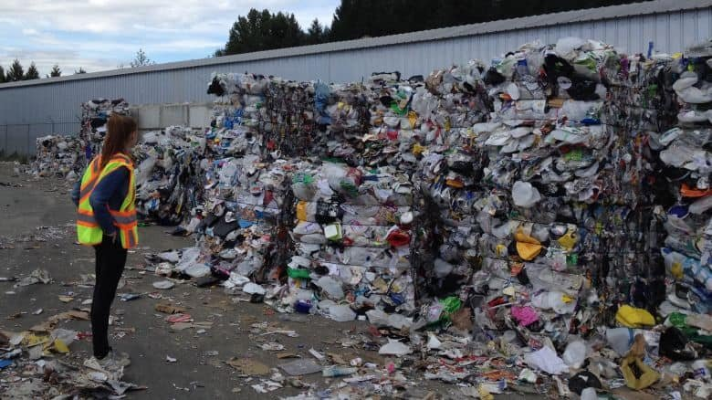 someone standing next to a pile of recycling materials