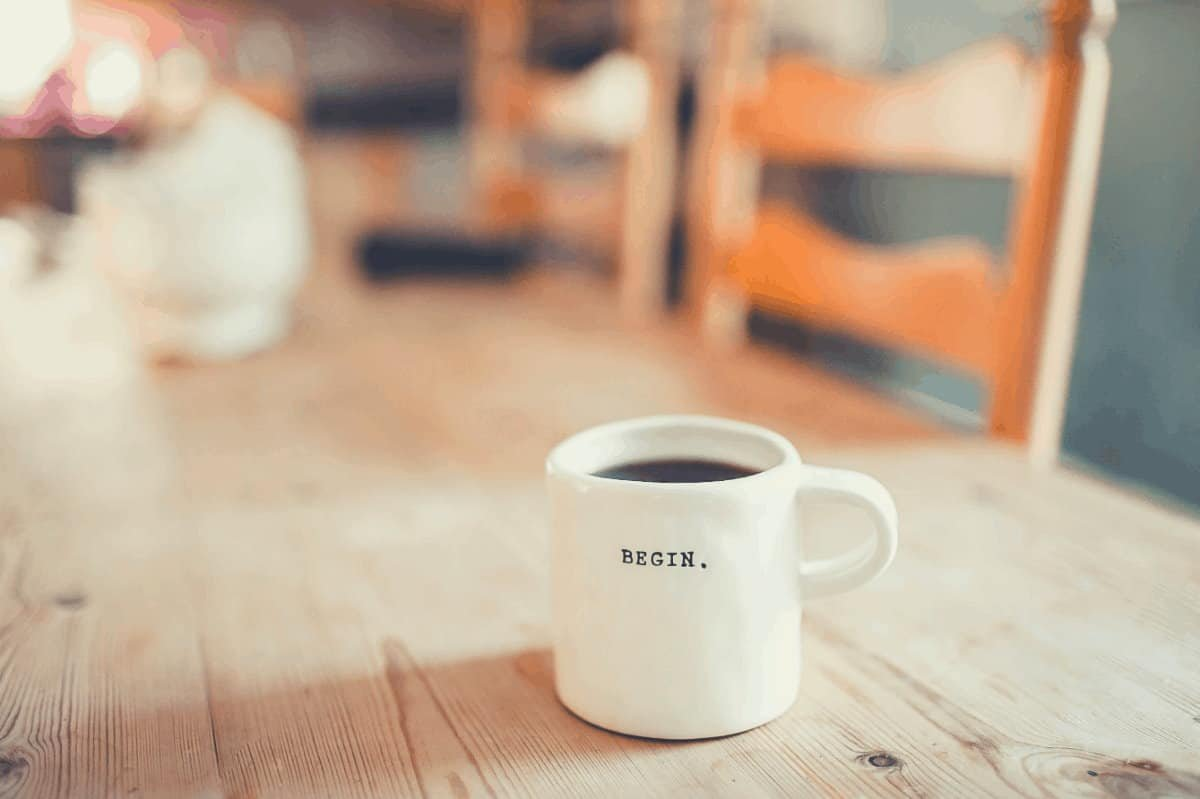 a photo of a coffee cup on a wooden table with chairs