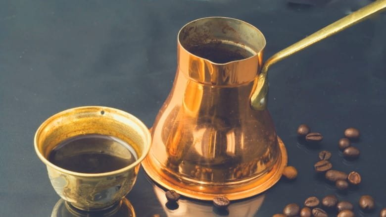 A picture of a brass cezve and cup