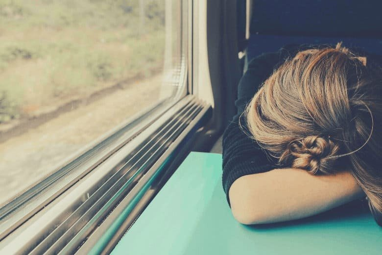 someone sleeping with their head on the table on a train