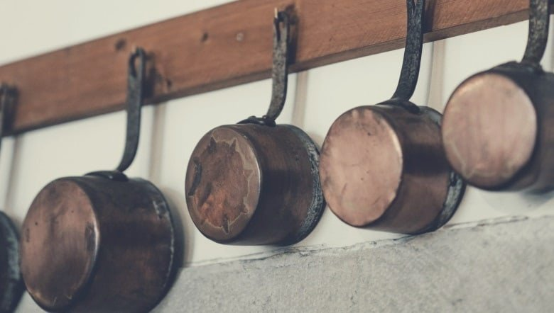various pots and pans hanging from a rack