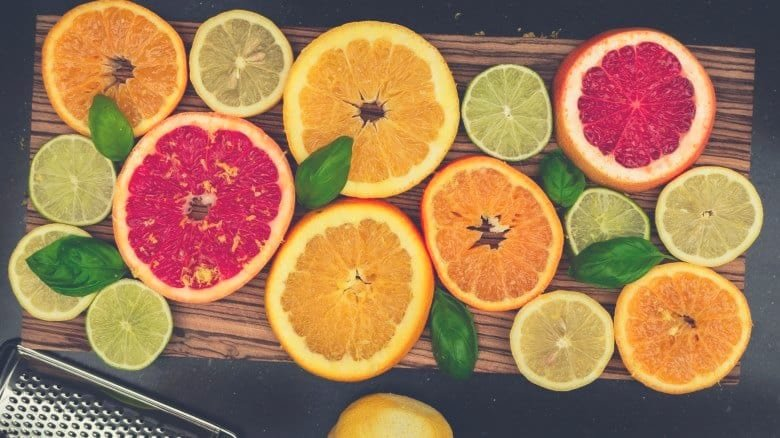 overhead shot of sliced citrus fruits on a wooden chopping board
