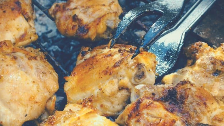chicken being cooked on a barbecue grill