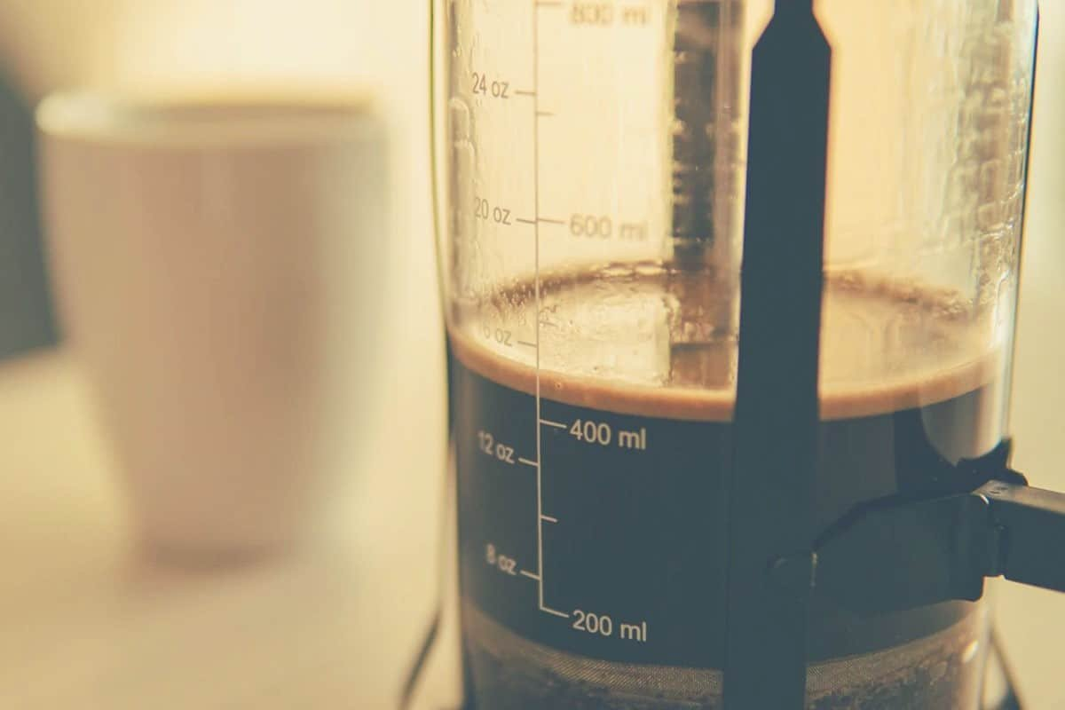 a close up shot of a cafetiere filled with coffee and a cup in the background