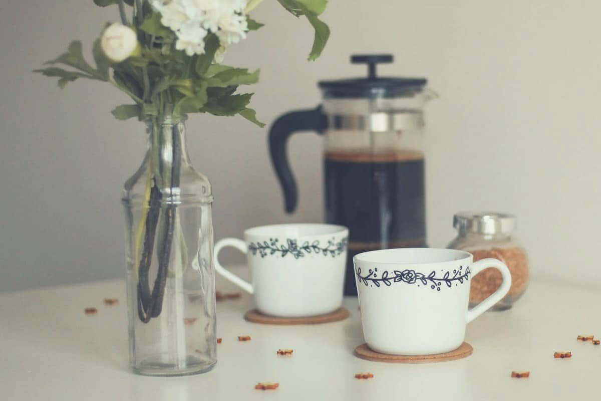 a cafetiere, two cups and flowers in a vase