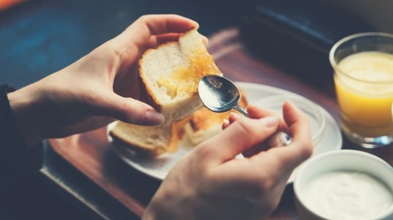 An overhead shot of someone spooning honey onto toast