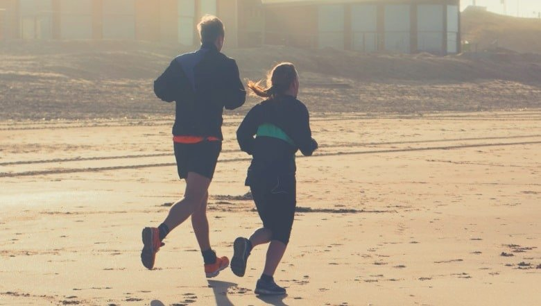 Two people jogging on a beach