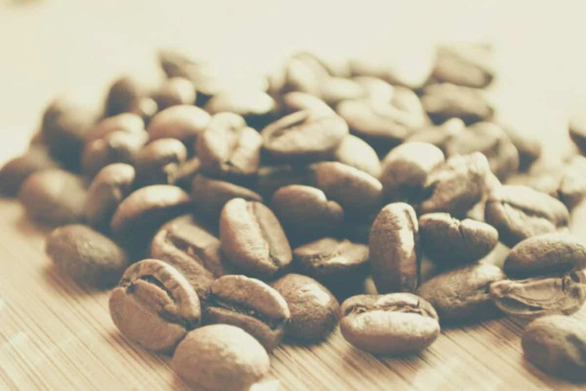 A pile of light roasted coffee beans on a wooden countertop