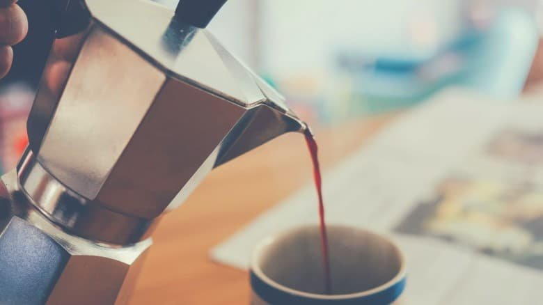 Coffee being poured from a Moka pot into a cup.