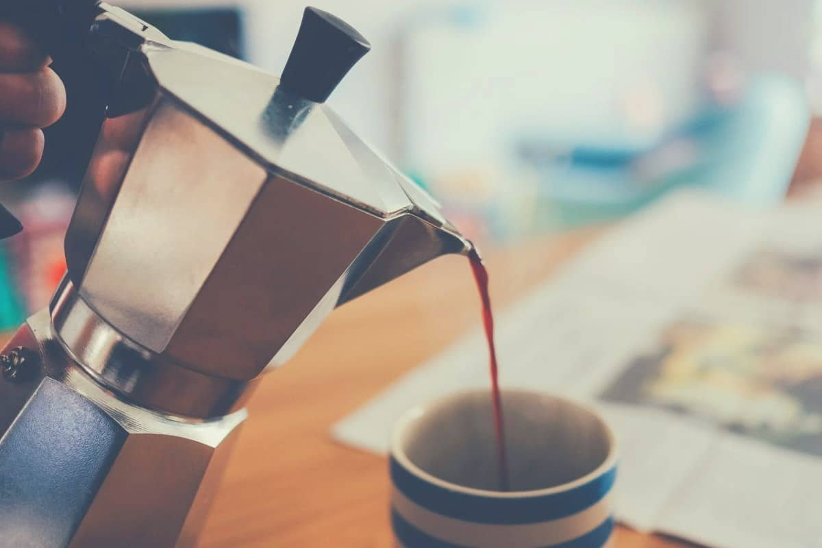 Coffee being poured from a Moka pot into a cup, with a newspaper on the table