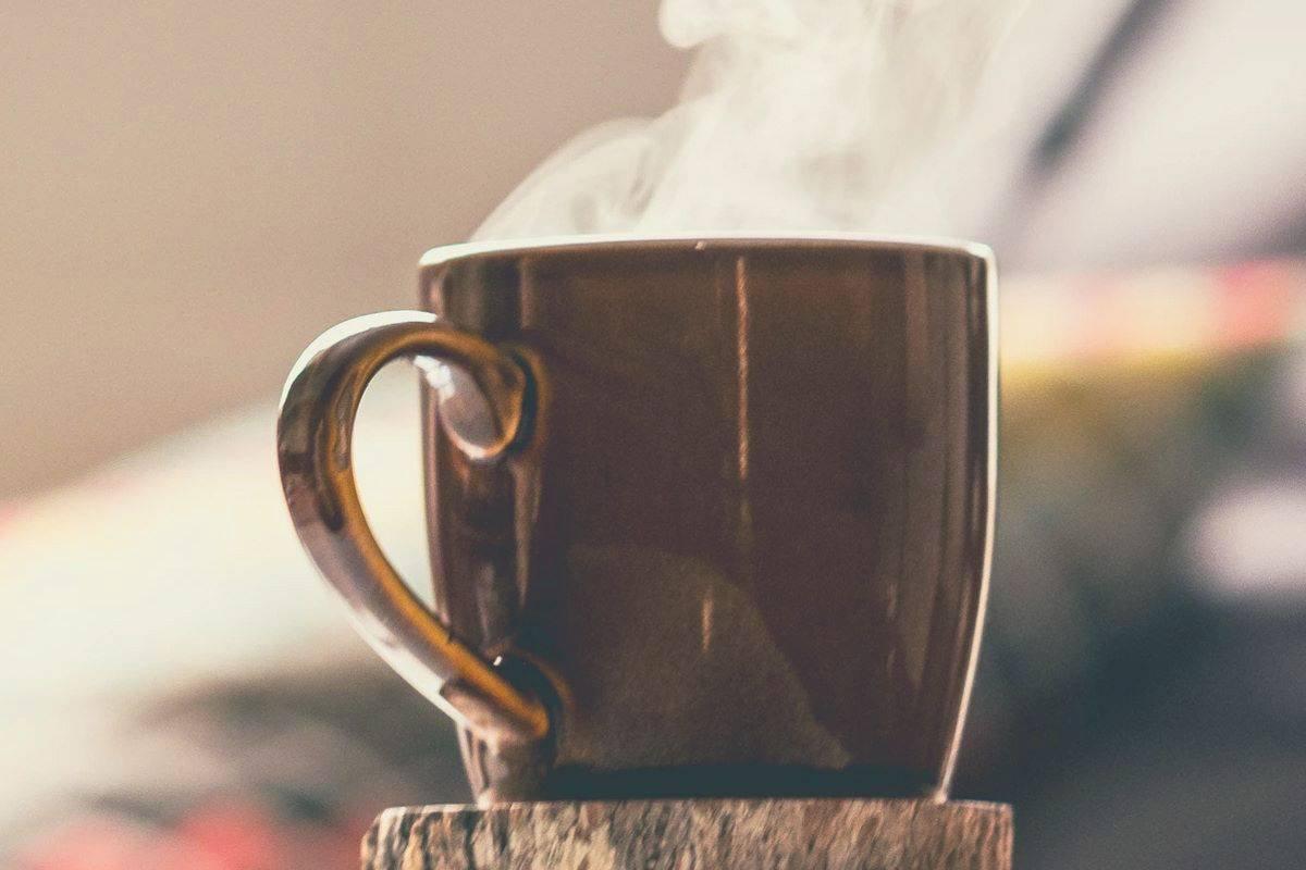 A steaming hot mug of coffee sitting on a coaster