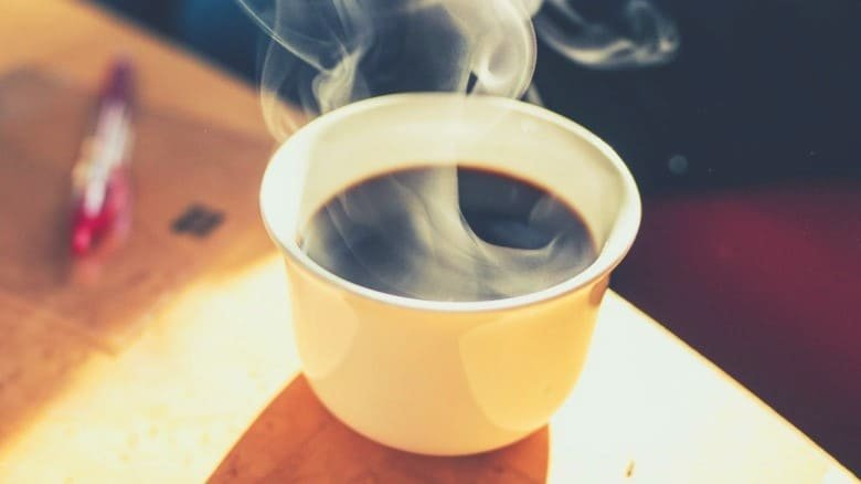 a steaming hot cup of coffee on a wooden table