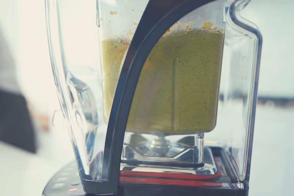 A close up shot of the Blendtec Professional 800 blending green ingredients