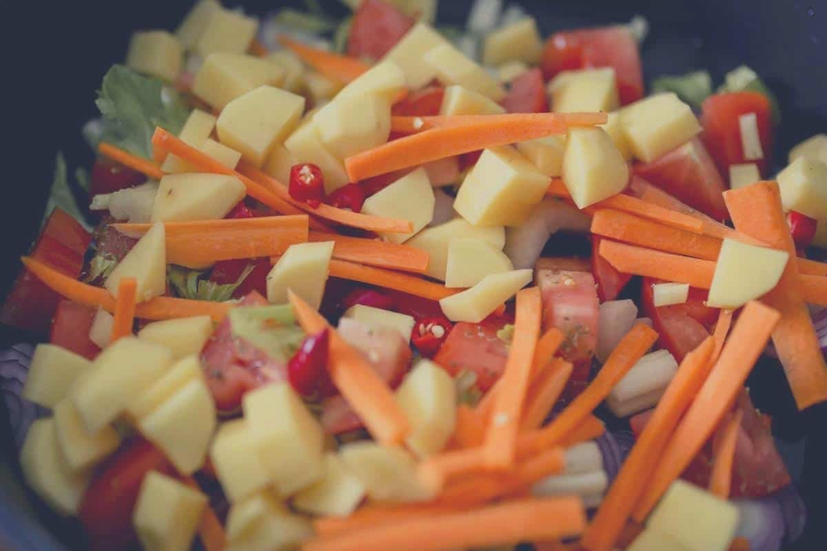 A big pile of chopped raw vegetables in a stone bowl