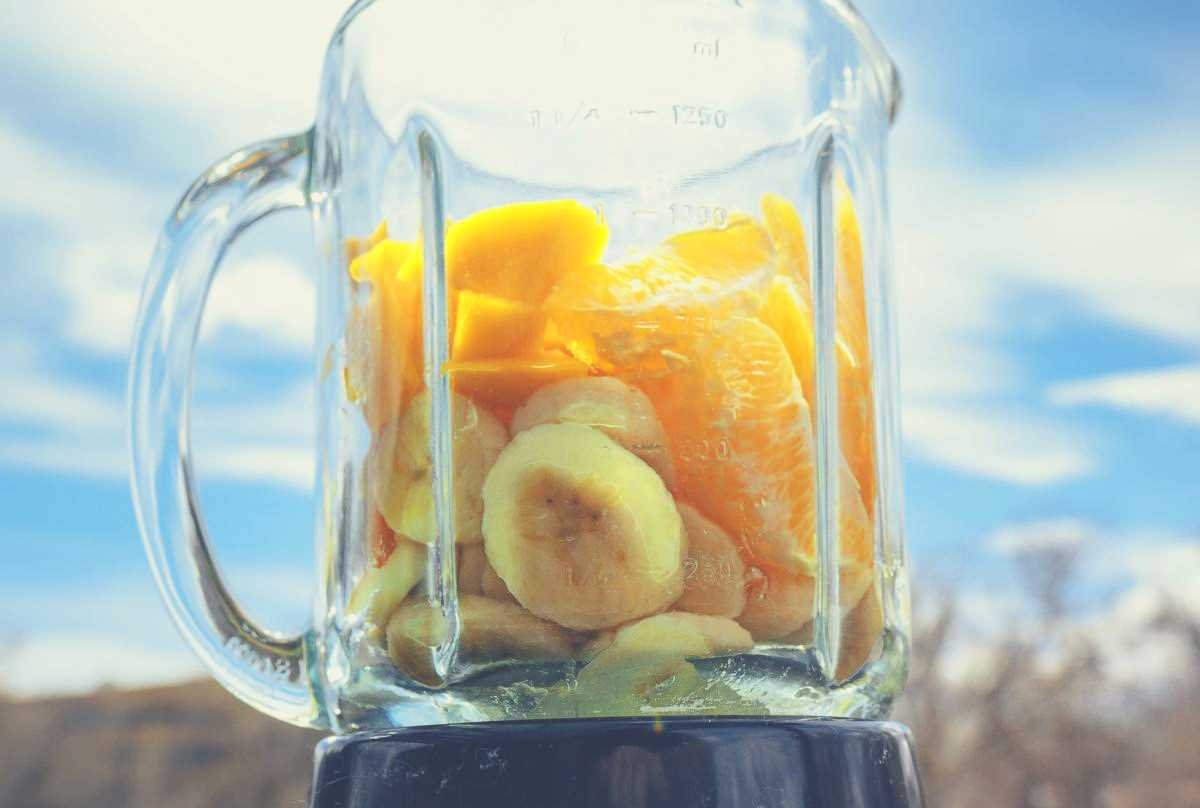 banana and pineapple in a glass blender against a cloudy blue sky