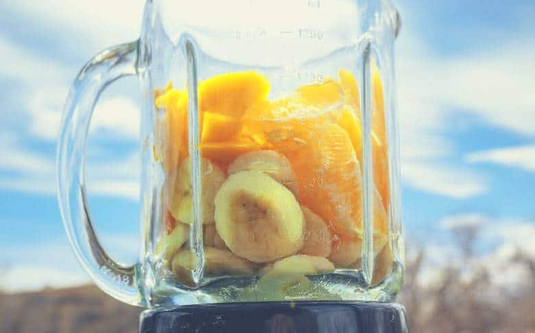 Bananas and pineapple in a glass jar blender with a blue sky background