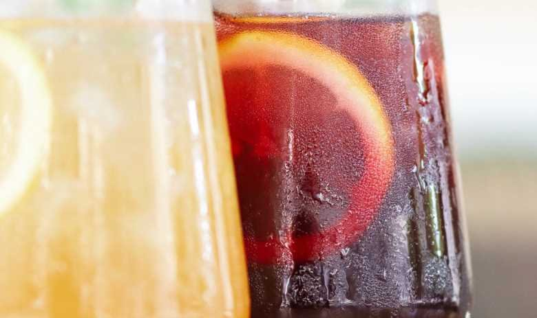 Two glasses of freshly squeezed fruit juice next to each other in a closeup