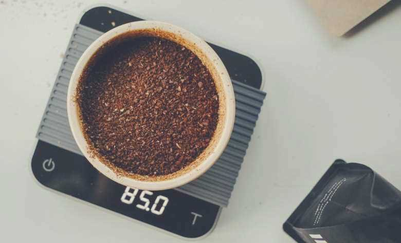 Coffee grounds in a white ceramic bowl being weighed on a set of digital scales