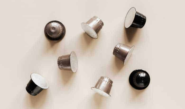 A selection of coffee pods scattered on a beige countertop