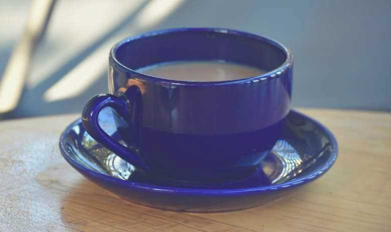 A blue coffee cup on a blue saucer