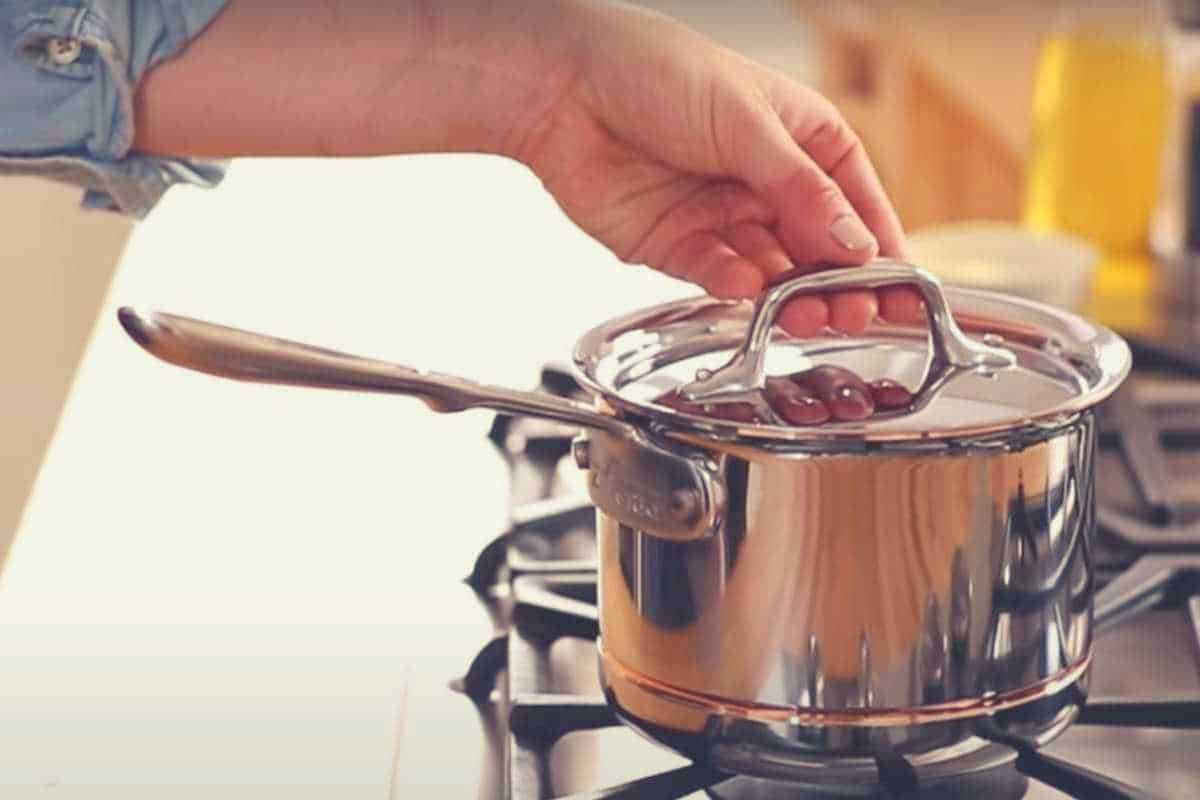 A lid being placed on an All-Clad Copper Cookware pan on the hob