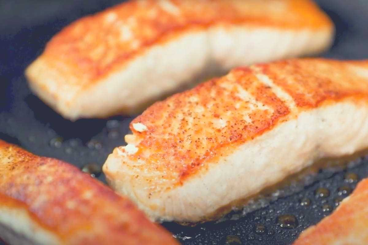 A picture of golden fish fillets cooking in an anodon advanced pan
