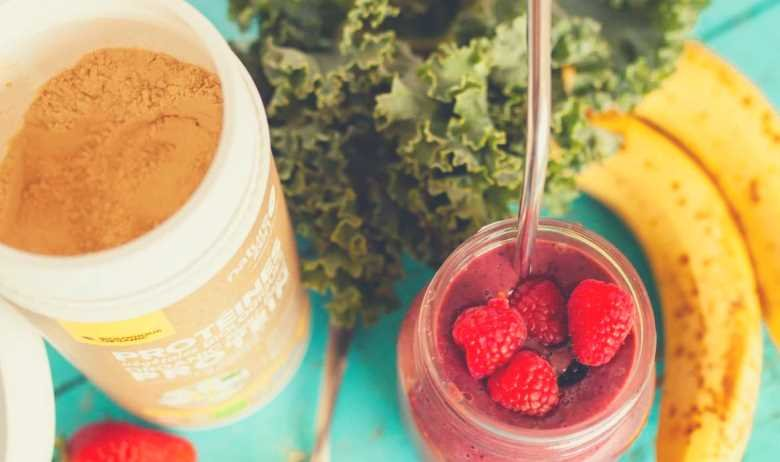 fresh fruit and vegetables being combined to make a protein shake