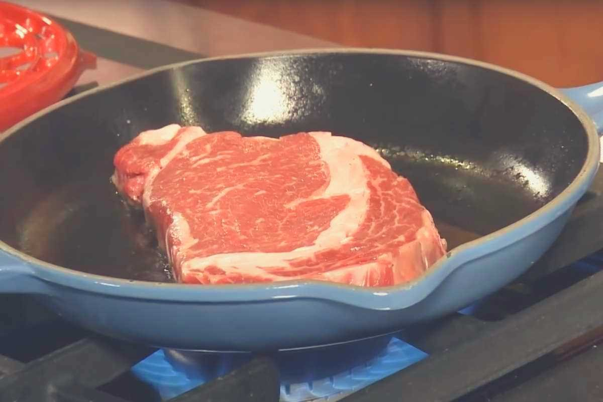 A steak cooking on a gas stovetop in a blue Le Creuset skillet