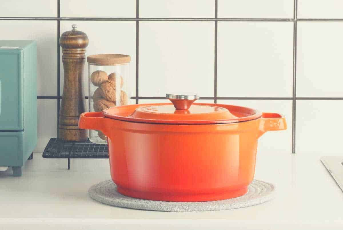 An orange Dutch oven resting on a kitchen countertop