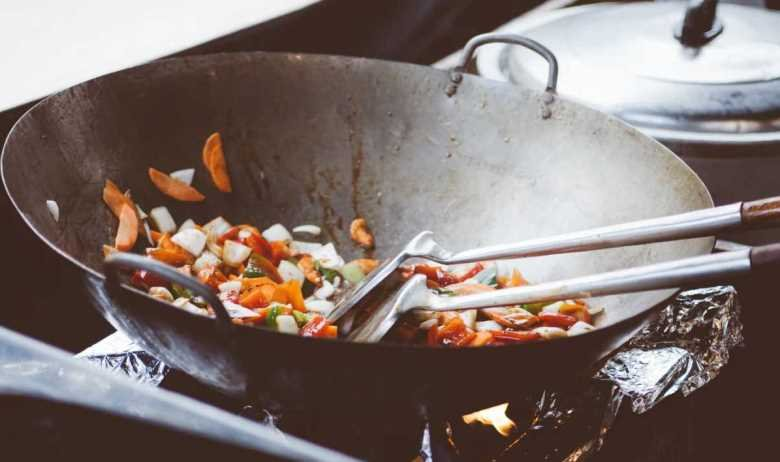 Vegetables being stir fried in a wok over a gas stovetop