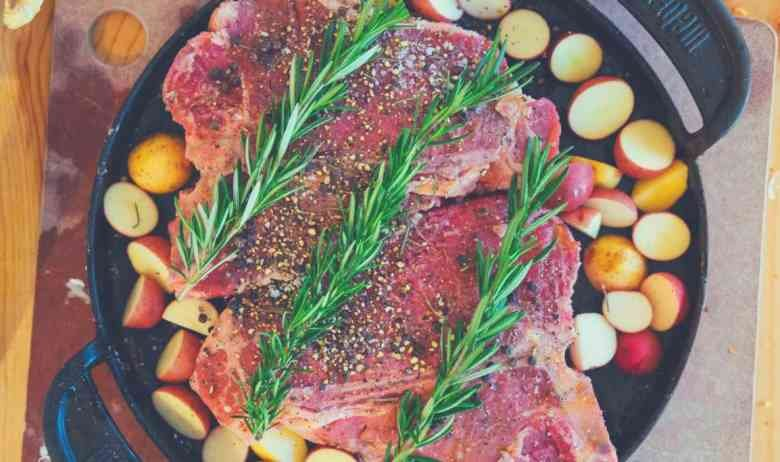 A large cut of meat covered in fresh rosemary and surrounded by vegetables in a skillet