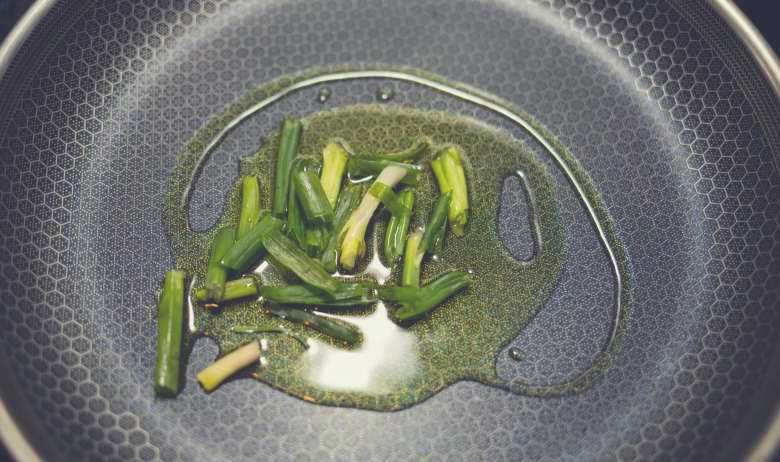 Green vegetables in oil, sitting on a non-stick cooking surface