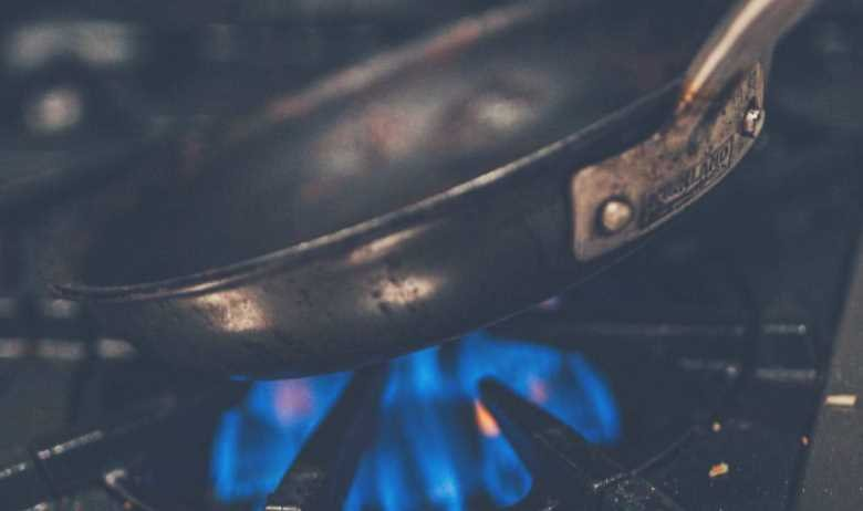A frying pan being held close to the heat of a gas stove hob