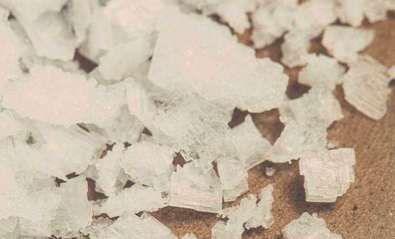 A close up shot of chunky table salt crystals on a wooden surface