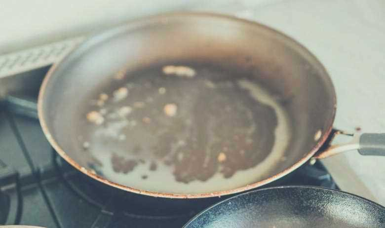 A greasy frying pan sitting on a gas stovetop