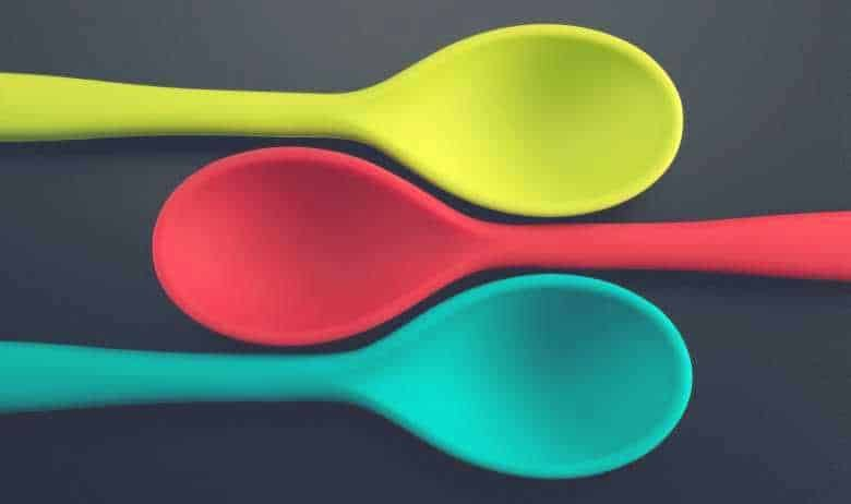 three yellow, red and blue silicone cooking utensils laid down above one another