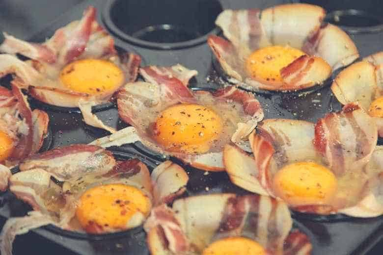 Raw eggs and bacon sitting in the cups of a muffin pan