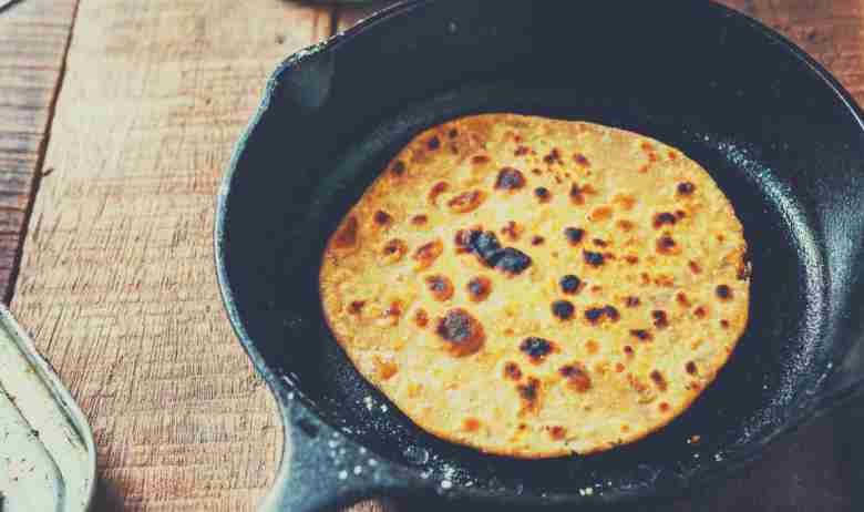 A crepe in a cast iron skillet which is sitting on a wooden kitchen countertop