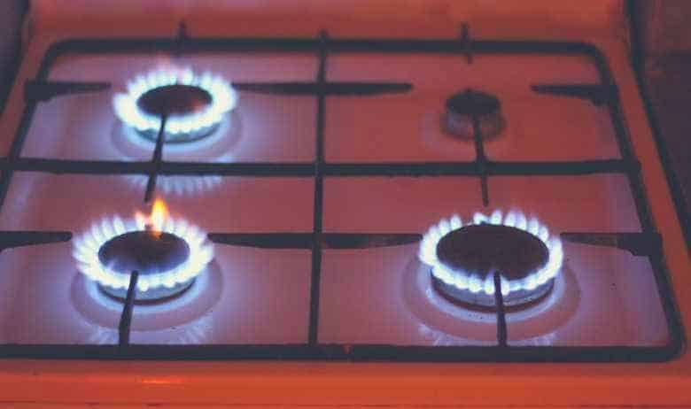 Three of four gas hobs lit on a gas stovetop