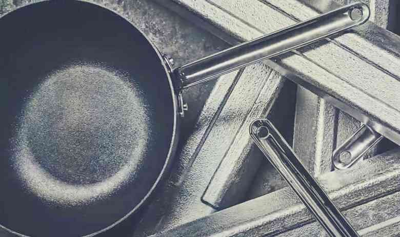 A Scanpan frying pan sitting on top of a collection of stainless steel bars