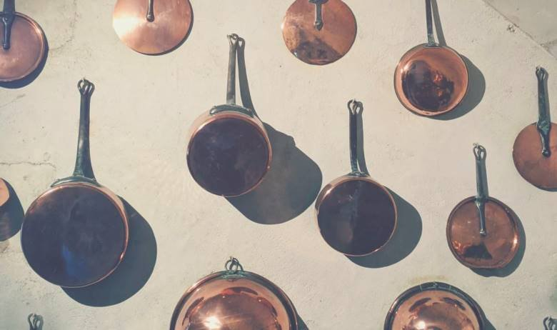 Many true copper pots and pans hanging from hooks on a kitchen wall