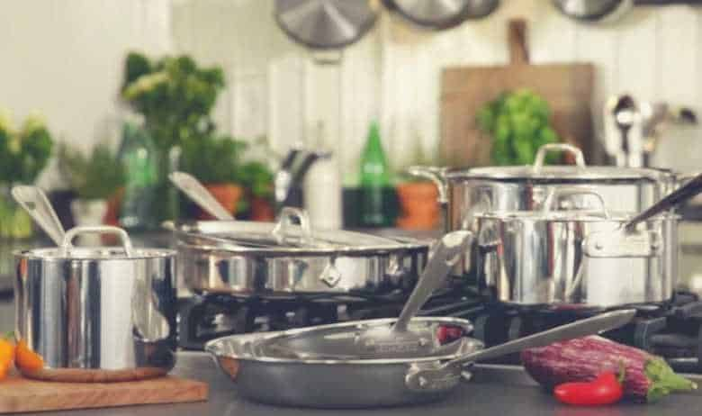 All-Clad cookware on a kitchen surface, with more pans suspended from a rack behind