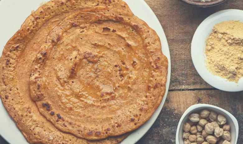 Two dosas on a white plate, next to spices, chickpeas and rice