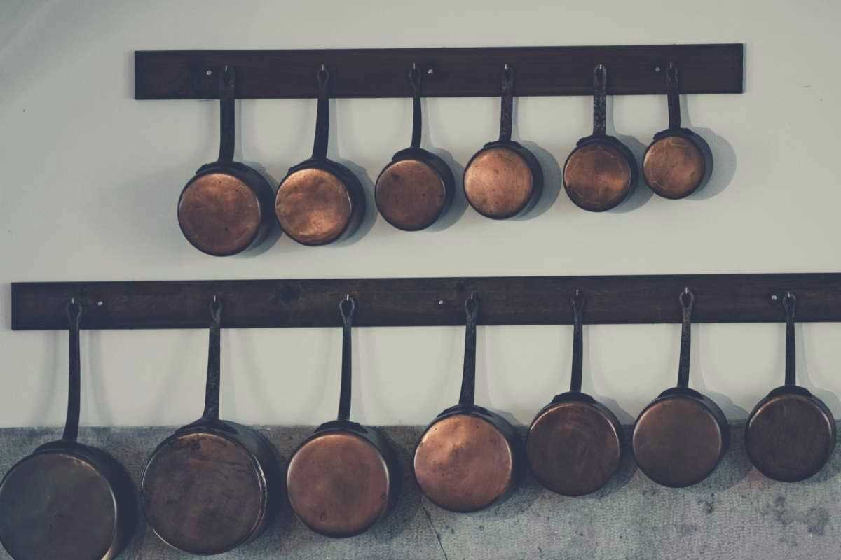 A collection of copper pots and pans hanging from two racks in a kitchen