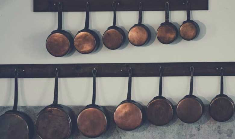 Lots of different copper pots and pans hanging from a pair of racks