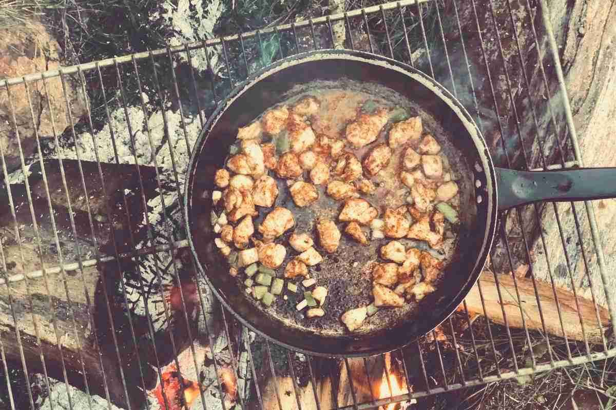 A top-down view of food cooking in a skillet over a campfire
