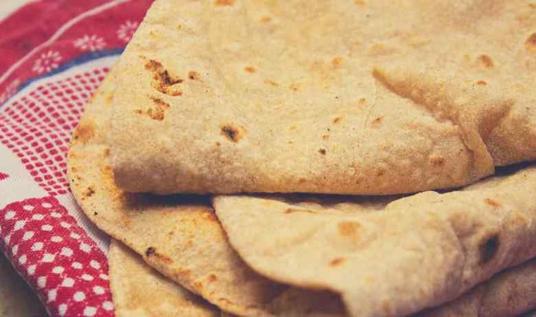 Freshly prepared tortillas sitting on a red checkered tablecloth