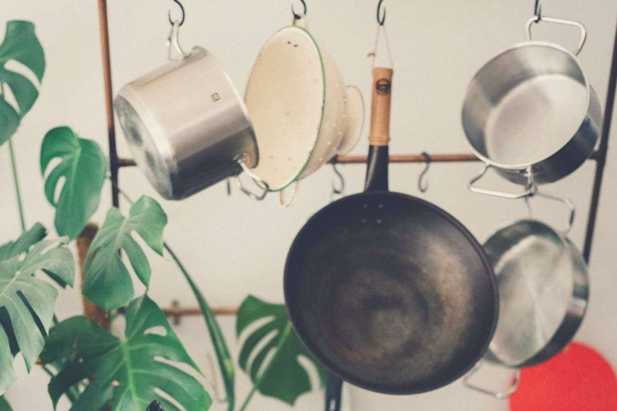 A collection of pots and pans hanging from a cookware rack, with a leafy green plant nearby