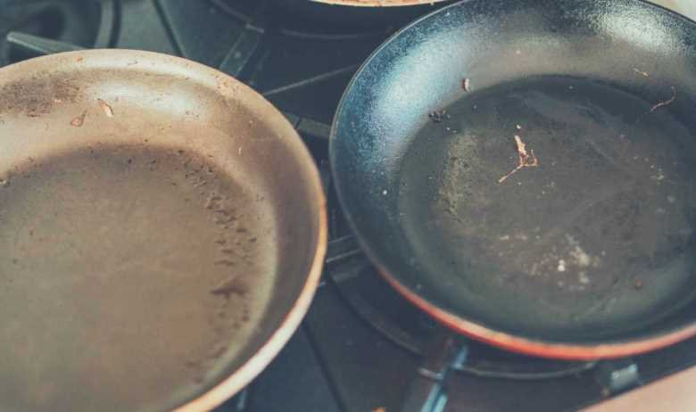 Two rusty pans, dirty from cooking, on a gas stove hob